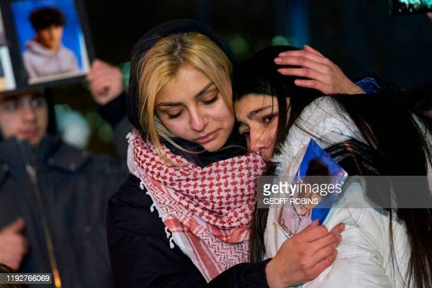 TOPSHOT Mourners console each other during a vigil for the victims of Ukrainian Airlines flight 752 which crashed in Iran during a vigil at Mel...