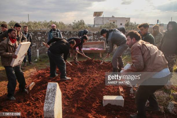 TOPSHOT Mourners cover the body of man killed after a reported proregime bombardment during his funeral in the village of Kafr Taal in Aleppo's...