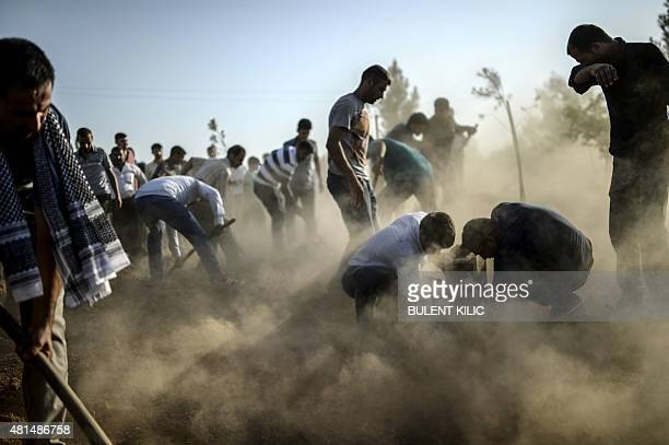 Mourners cover the graves of victims of a suicide bomb attack during their funeral in Suruc in Turkey's Sanliurfa province on July 21 2015 Turkey...