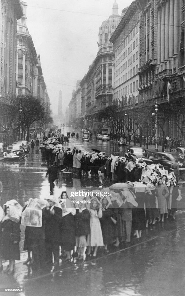 Mourners cover their heads with newspapers as they queue in the rain outside the Ministry of Labour building in Buenos Aires to see the body of Argentine First Lady Eva Peron (1919 - 1952) lying in state, 1st August 1952.
