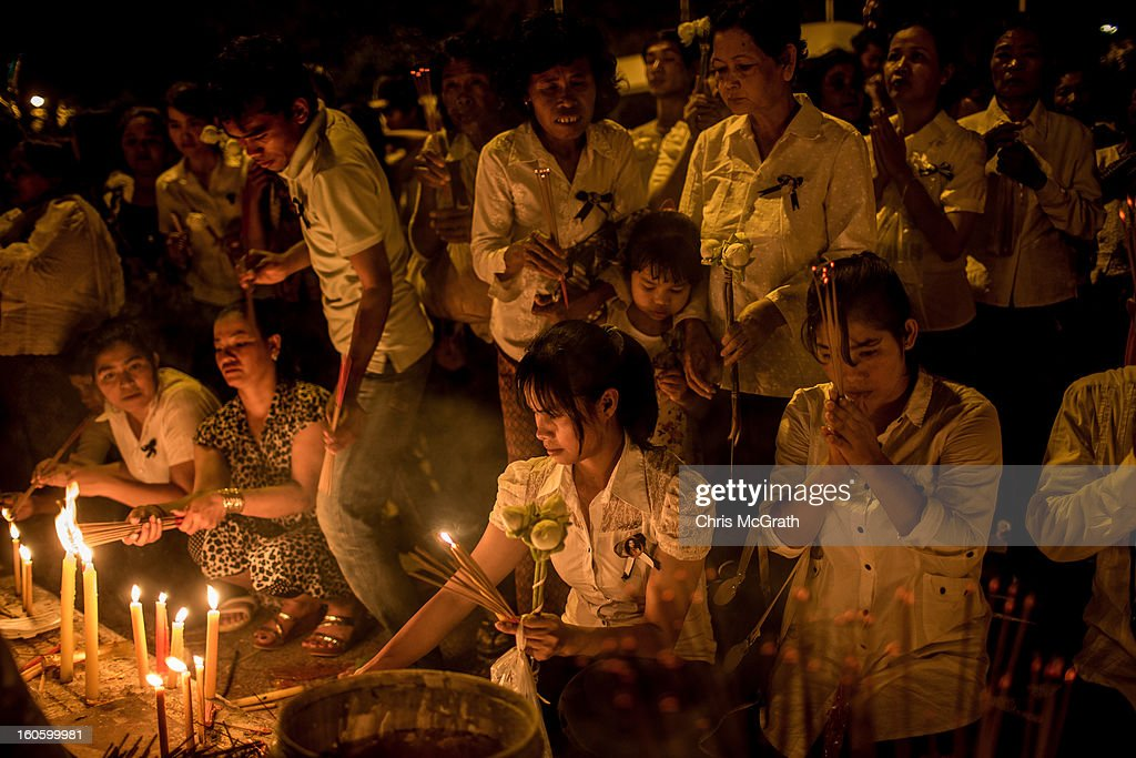 Mourners crowd around candles to light incense at the cremation site on the eve of the cremation of former King Norodom Sihanouk on February 3, 2013 in Phnom Penh, Cambodia. The former kings coffin was transported to the cremation site after being paraded through the capital in a lavish funeral procession. The cremation will take place on Monday the 4th of February, the funeral pyre will be lit by his wife and son King Norodom Sihamoni.