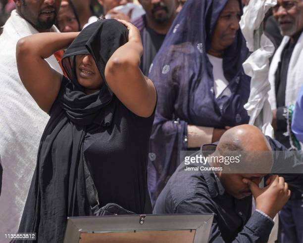 Mourners cry as they look at photos of crew members during a memorial at the crash site of Ethiopian Airlines Flight ET302 on March 14 2019 in Ejere...