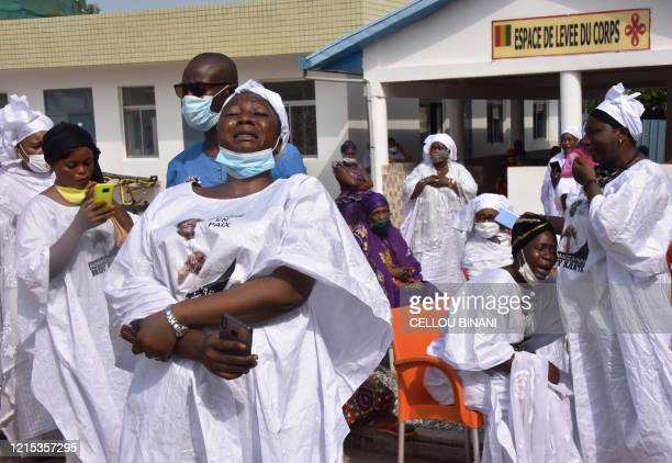 Mourners cry during the funeral of the late Guinean singer Mory Kante on May 26 2020 in Conakry Guinea Hundreds of people gathered to mourn the death...