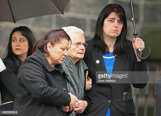 Mourners embrace as they leave after attending a national memorial service as Australians mourn the loss of all victims of Malaysia Airlines Flight...