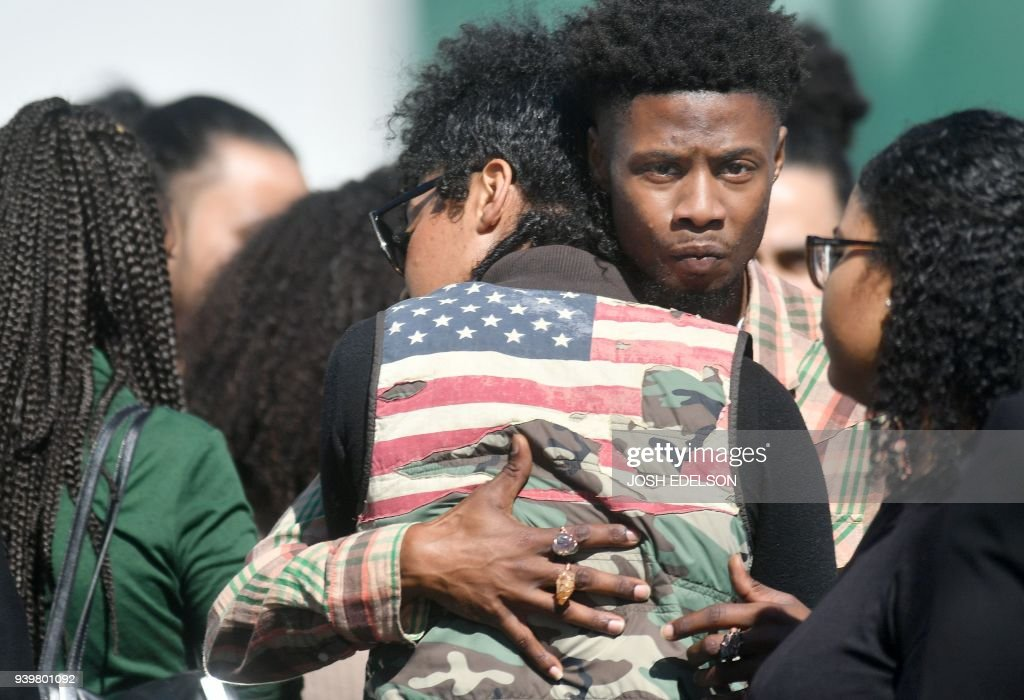 TOPSHOT - Mourners embrace as they wait to enter Stephon Clark's funeral in Sacramento, California on March 29, 2018. Stephon Clark, an unarmed African American, was shot and killed by police on March 18, 2018 at his grandmother's home. /