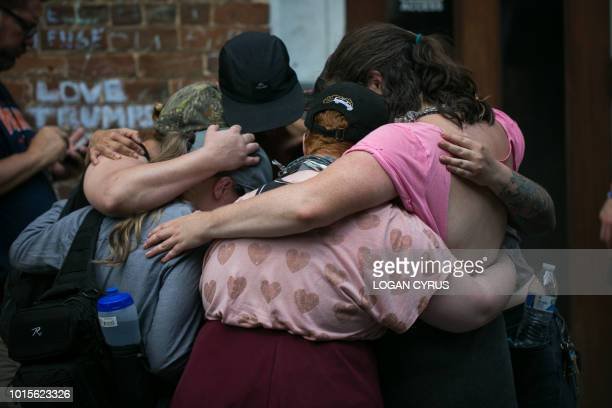 Mourners embrace before the makeshift memorial to Heather Heyer August 12 2018 in Charlottesville Virginia on the one year anniversary of her death...