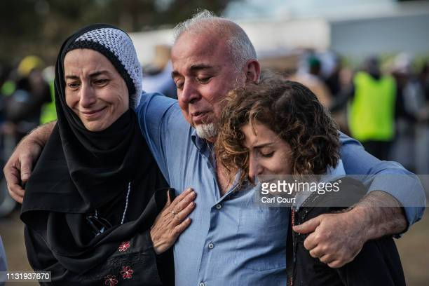 Mourners embrace each other as they leave after attending the funeral of a victim of the Christchurch mosque attacks at Memorial Park Cemetery on...