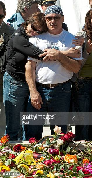 Mourners embrace in front of a reflecting pool at Ground Zero during the annual 9/11 memorial service September 11 2010 in New York City People...