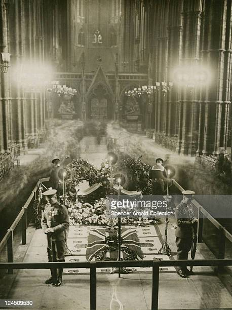 Mourners file past the tomb of The Unknown Warrior which is being guarded by four British servicemen at Westminster Abbey London 1920