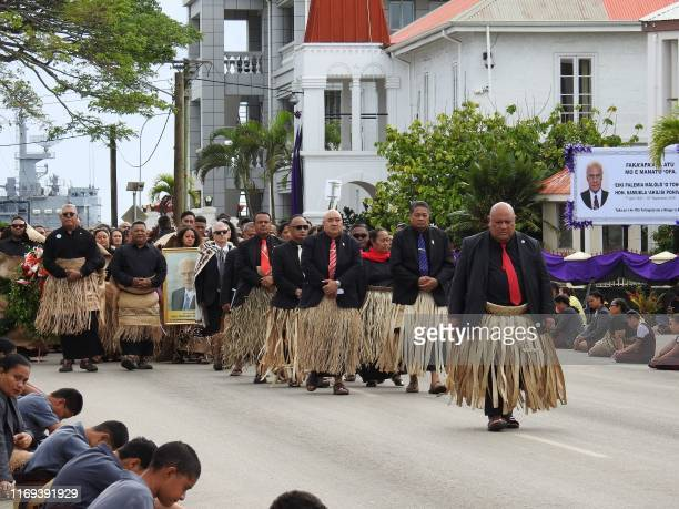 Mourners follow the hearse carrying the body of Tonga's late prime minister Akilisi Pohiva as it is driven through the capital Nuku'alofa on...