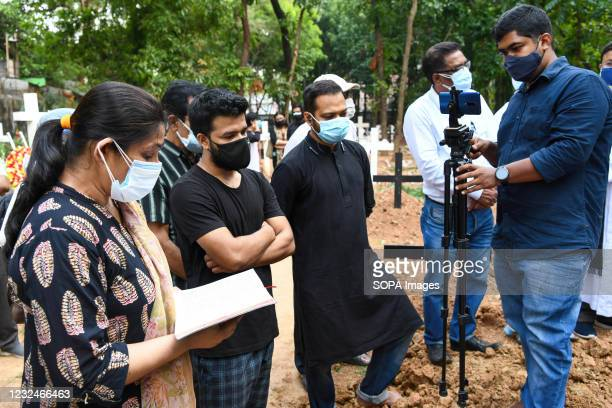 Mourners for the covid 19 deceased man during a burial by Bangladeshi Christians at a cemetery.