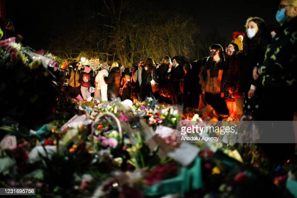 Mourners for the life of murdered 33-year-old Sarah Everard, whose remains were found this week in woodland in Kent, stand around floral tributes as...