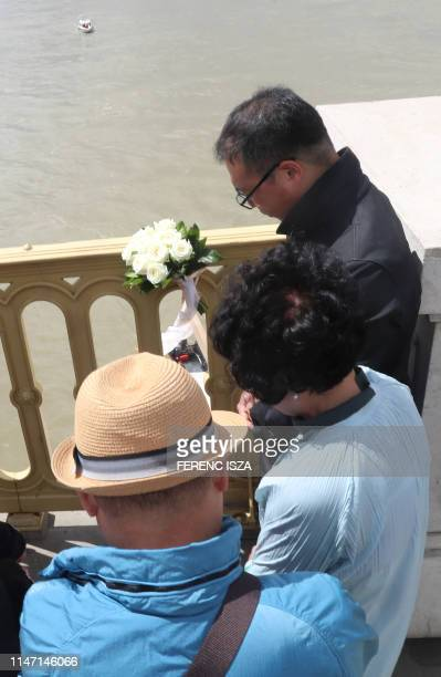 Mourners from South Korea bring flowers and candles on the bridge over the Danube on May 31 2019 in Budapest near the spot of a boat accident with...