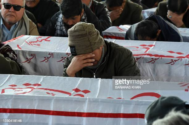 Mourners from the Shiite Hazara community gather near the coffins of the miners who were killed in an attack by gunmen in the mountainous Machh area,...