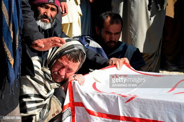 Mourners from the Shiite Hazara community sit next to the coffin of one of the miner, who was killed in an attack by gunmen in the mountainous Machh...