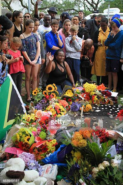 Mourners gather around flowers and tributes outside the home of former South African President Nelson Mandela following the announcement of his death...