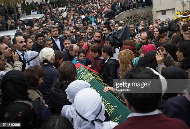 Mourners gather around the coffin of Sarigul Tuylu a mother of two that was killed in Saturday's bombing attacks in Ankara, Turkey, during her...