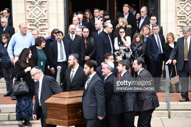 Mourners gather as a casket is carried outside the Rodef Shalom Congregation where the funeral for Tree of Life Congregation mass shooting victims...