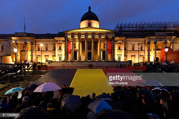Mourners gather as a giant Belgian Flag is draped down the stairs of Trafalgar Square as a candlelit vigil takes place in support of the victims of...