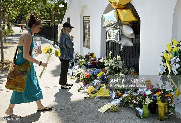Mourners gather at a makeshift memorial outside the Emanuel AME Church in Charleston, South Carolina on June 18 after a mass shooting at the church...