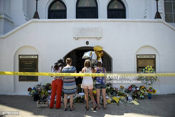 Mourners gather at a makeshift memorial outside the Emanuel AME Church in Charleston South Carolina on June 18 after a mass shooting at the church...