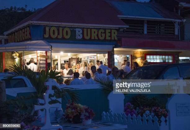 Mourners gather at Jojo Burger after the burial of French rock icon Johnny Hallyday at the Lorient Cemetery in Saint Barthélemy on December 11 2017...