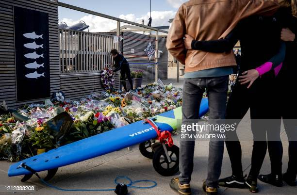 Mourners gather beside floral tributes during a commemeration at The Shore Surf Club at Scheveningen, The Hague on May 13 held to remember five...