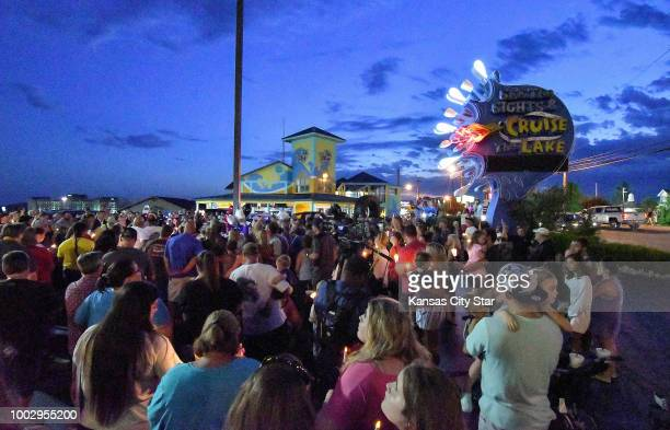 Mourners gather in the parking lot of the Ride the Ducks offices in Branson Mo during a candle light vigil on Friday July 20 2018 for the victims of...