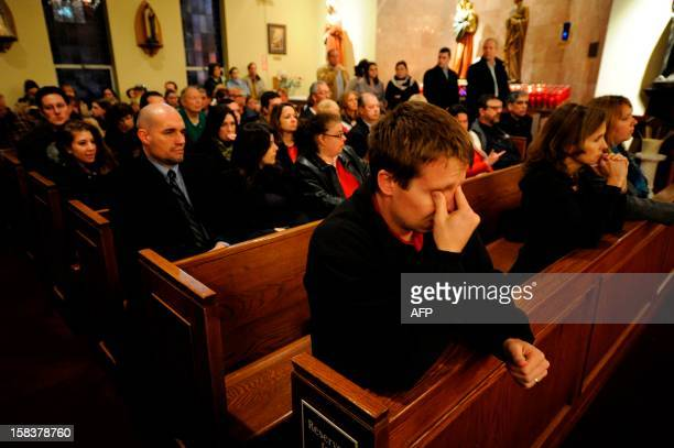 Mourners gather inside the St. Rose of Lima Roman Catholic Church at a vigil service for victims of the Sandy Hook Elementary School shooting that...