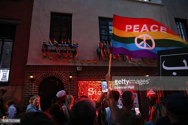 Mourners gather outside of the iconic New York City gay and lesbian bar the Stonewall Inn to light candleslay flowers and grieve for those killed in...