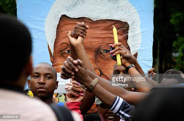 Mourners gather outside the home of former South African President Nelson Mandela following the announcement of his death in Johannesburg South...