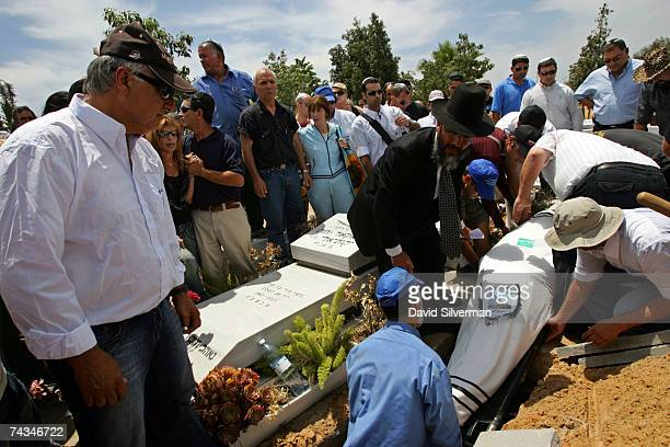 Mourners gather round the grave as the shroudwrapped body of Qassam rocket victim Oshri Oz is laid to rest May 28 2007 in Yarkon cemetery in Petah...