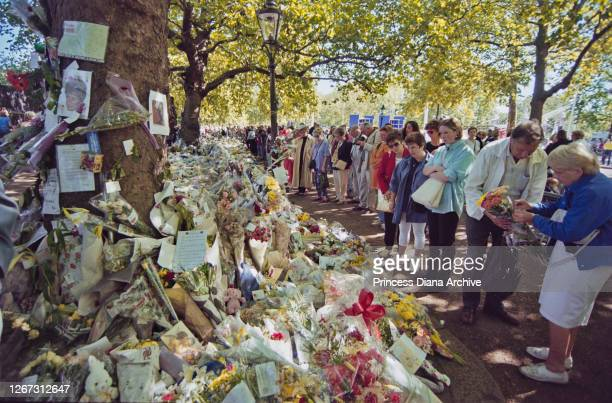 Mourners gather to leave floral tributes and messages of condolence in memory of British Royal Diana Princess of Wales are left outside Buckingham...