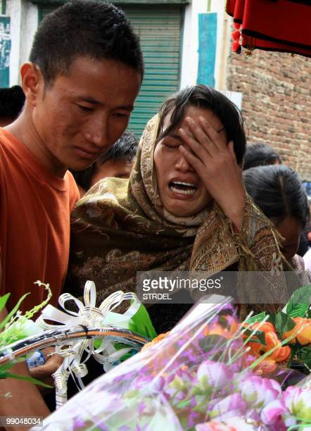 Mourners gather to pay their respects at the funeral of two Naga students Chakho and Loshuo as it passes through Mao Gate the town which straddles...