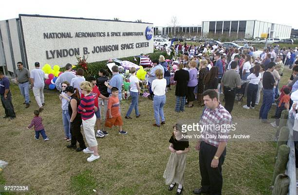 Mourners gather to pray and grieve at a tribute of flowers and flags outside the Johnson Space Center in Houston in memory of the seven astronauts...