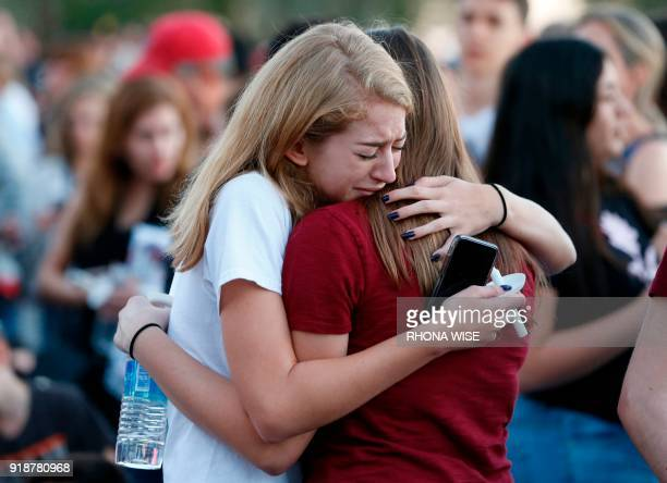 Mourners grieve as they await the start of a candlelight vigil for victims of the Marjory Stoneman Douglas High School shooting in Parkland Florida...
