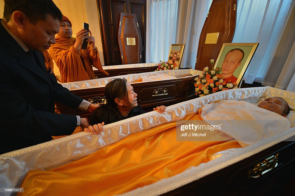 Mourners grieve beside the open coffins at a service of remembrance for three thai Buddhist Monks who died in a car crash on Christmas Eve, at Oakvale Funeral Home on January 2, 2013 in Edinburgh, Scotland. Abbot Phramaha Pranom Thongphaiboon, 43, head of the Thai Buddhist community in Aberdeen, was killed in a car crash on Christmas Eve along with his colleagues Phramaha Kriangkrai Khamsamrong, 35, and Phramaha Chai Boonma, 36. The three men were travelling to the Dhammapadipa Temple in Edinburgh when they were involved in the head-on collision on the A68 near Pathhead, Midlothian.