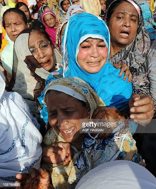 Mourners grieve during a funeral for shooting victims a day after an attack by gunmen at a market in Karachi on October 20 2010 Pakistan said there...