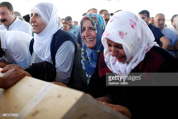 Mourners grieve over a coffin during a funeral ceremony for the victims of a suicide bomb attack yesterday which killed 32 people in the southern...