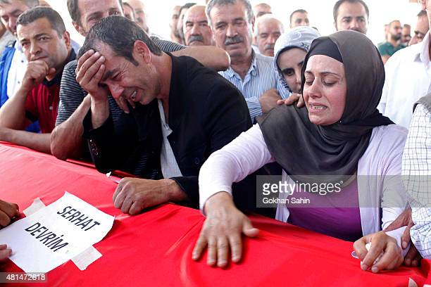 Mourners grieve over the coffin of Serhat Devrim during a funeral ceremony for the victims of a suicide bomb attack yesterday which killed 32 people...