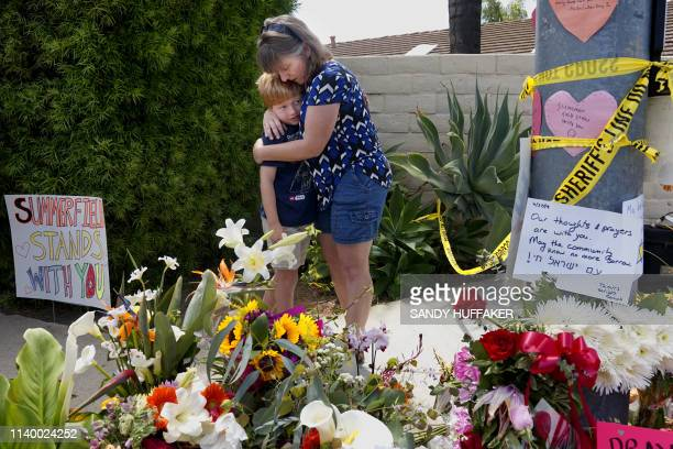 Mourners Heather Foy and her son Marshall, who live in the neighborhood, embrace at a make-shift memorial across the street from the Chabad of Poway...