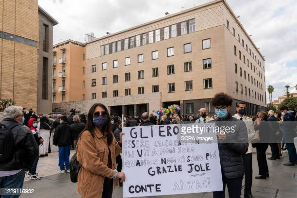 Mourners hold a placard during the funeral ceremony of the Calabria regional governor Jole Santelli at St. Nicholas Church in Cosenza. A funeral...