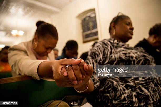 Mourners hold a prayer vigil for the nine victims of last night's shooting at the historic Emanuel African Methodist Episcopal Church in Charleston,...