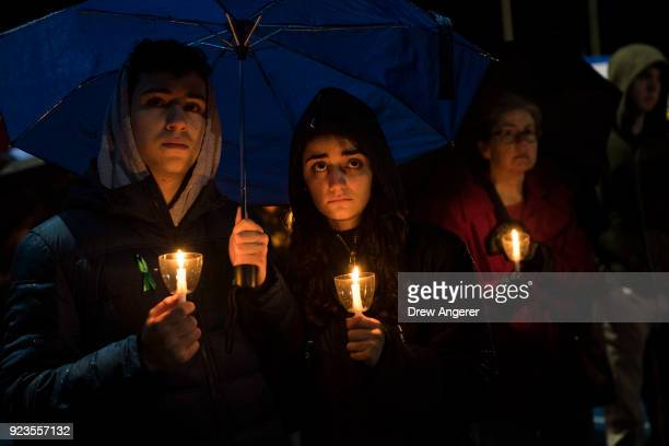 Mourners hold candles as they attend a community vigil at Newtown High School for the victims of last week's mass shooting at Marjory Stoneman...