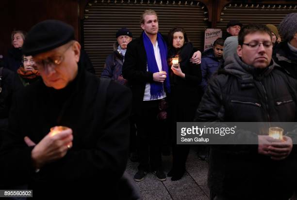 Mourners hold candles as they commemorate the first anniversary of the 2016 Christmas market terror attack at the attack site on December 19 2017 in...