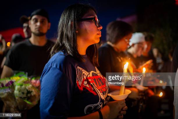 Mourners hold candles as they gather for a vigil at a memorial outside Cielo Vista Walmart in El Paso, Texas, U.S., on Wednesday, Aug. 7, 2019....