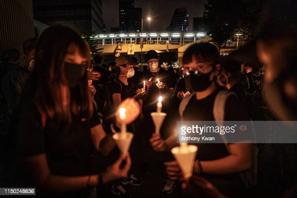 Mourners hold candles during a candlelight vigil to commemorate a protestor who died last night during a rally against a controversial extradition...