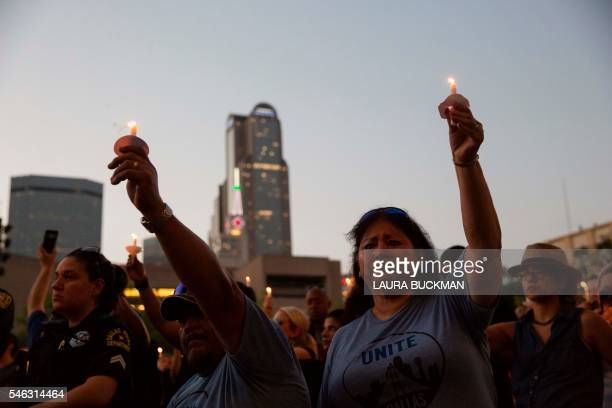 Mourners hold candles during a Dallas Strong vigil outside City Hall in Dallas Texas on July 11 held in honor of the five police officers killed in...