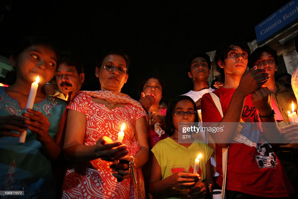 Mourners hold candles during a vigil for