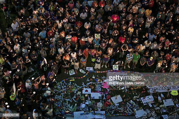 TOPSHOT Mourners hold candles while observing a moment of silence during a vigil outside the Dr Phillips Center for the Performing Arts for the mass...